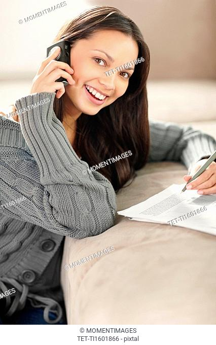 Woman talking on phone while doing paperwork