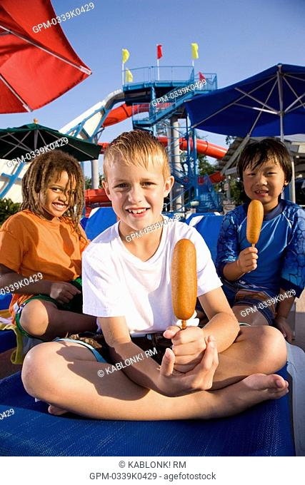 Multi-ethnic boys at water park in summer eating corn dogs