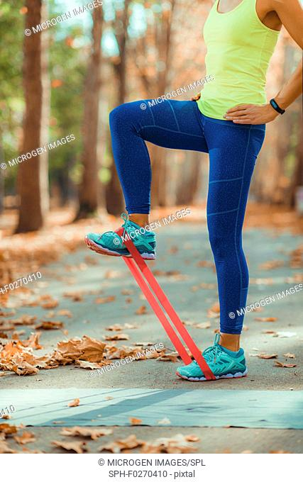 Woman exercising legs with resistance band outdoors