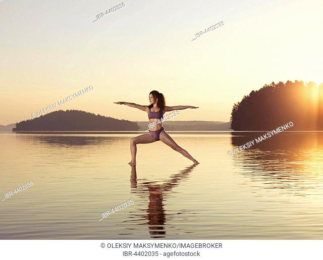 Young woman practicing Hatha yoga on a floating platform in water on a lake during sunrise, Yoga Warrior posture, Veerabhadrasana