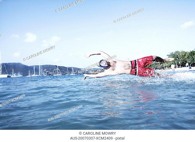 Mid adult man diving in water