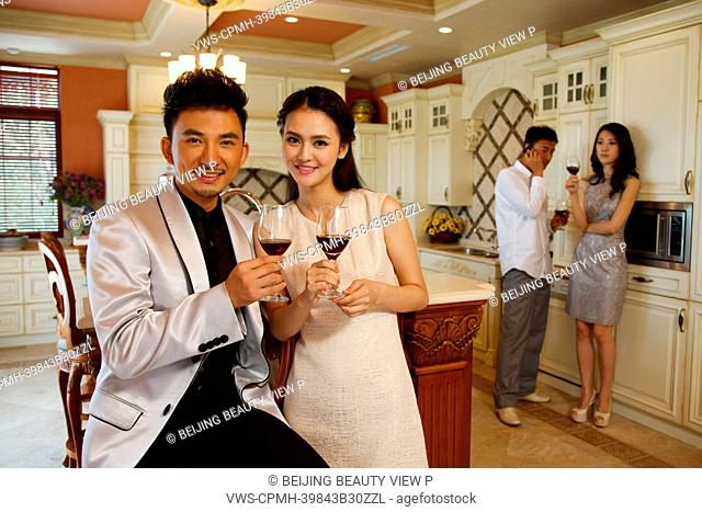 Young people holding glasses of red wine in kitchen