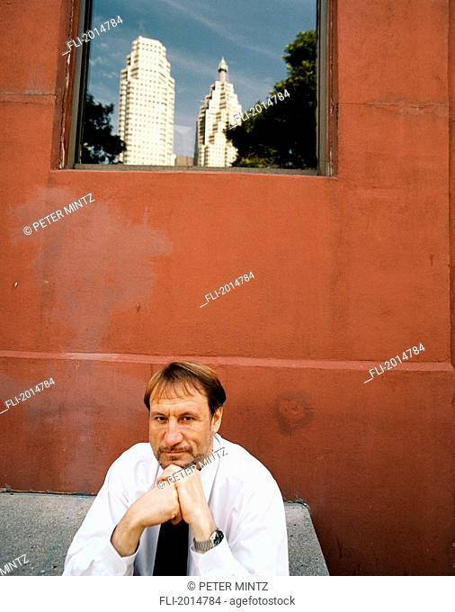 Businessman Sitting In Front Of Building, Toronto, Ontario