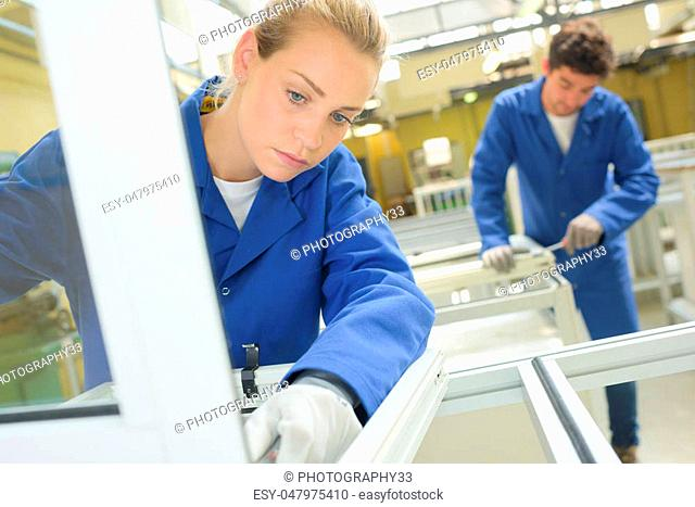 Young people working in window factory