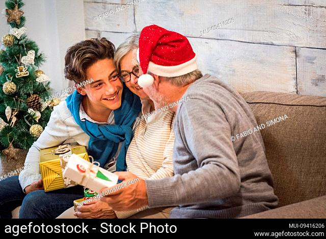 Mixed generations people celebrating christmas eve together at home - young teenager grandson or son and old grandfathers or parents with santa claus hat have...