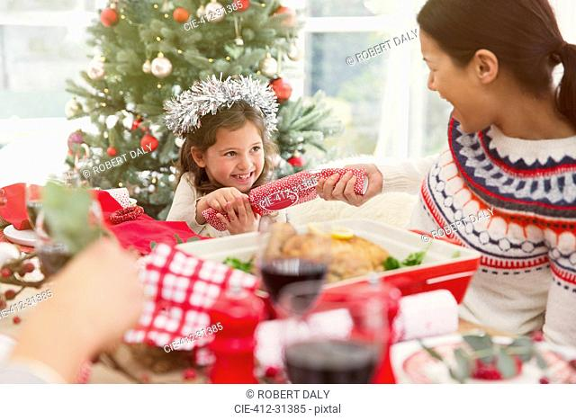 Mother and daughter pulling Christmas cracker at dinner table