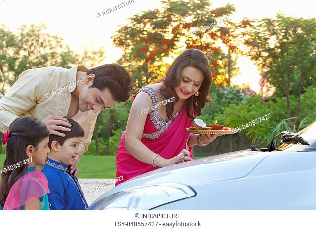 Woman putting tika on new car