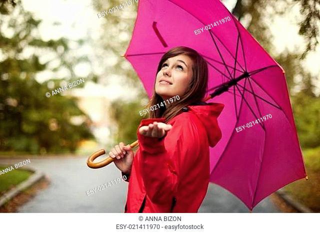 Beautiful woman with umbrella checking for rain