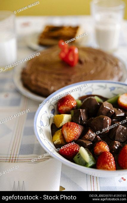 Tasty fruits and chocolate on table with birthday cake
