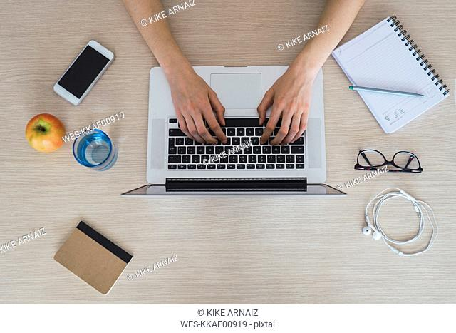 Top view of woman using laptop on table