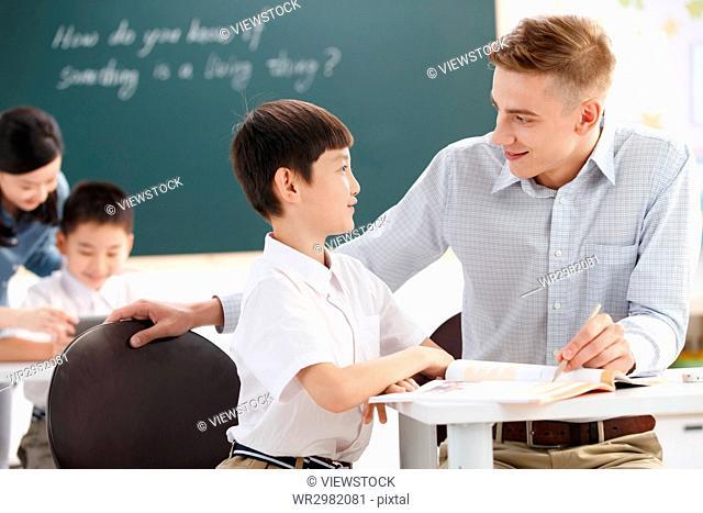 Male teacher helping student study