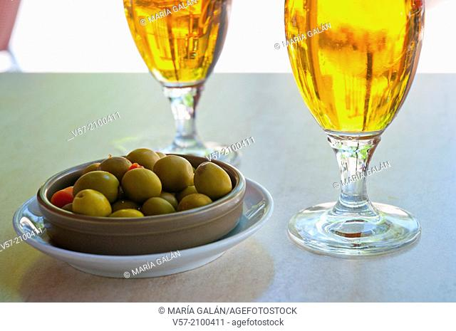 Spanish aperitif: two glasses of beer and green olives in a terrace. Spain