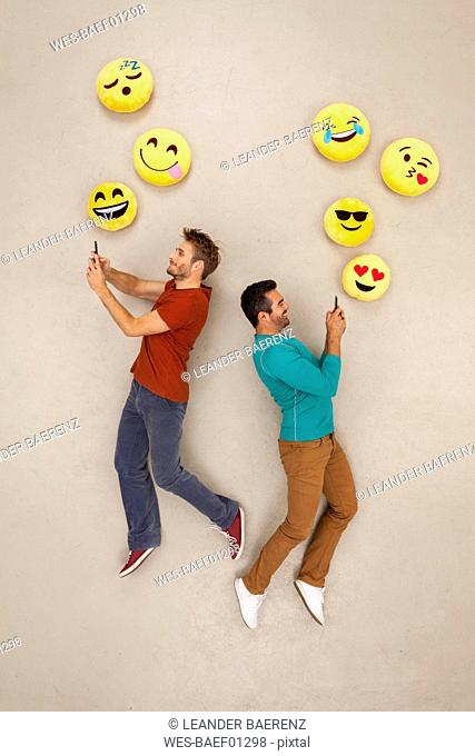 Friends chatting on their smart phones, sending emojies