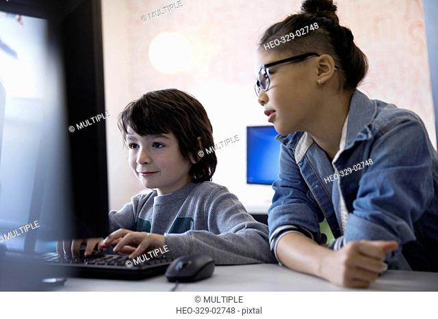 Pre-adolescent boy and girl using computer in classroom