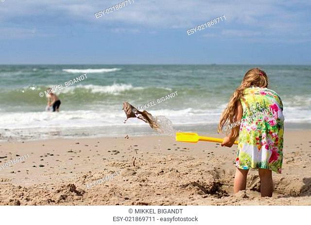 Girl in summer dress digging at beach