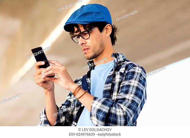 leisure, technology, communication and people concept - hipster man texting message on smartphone or playing augmented reality game