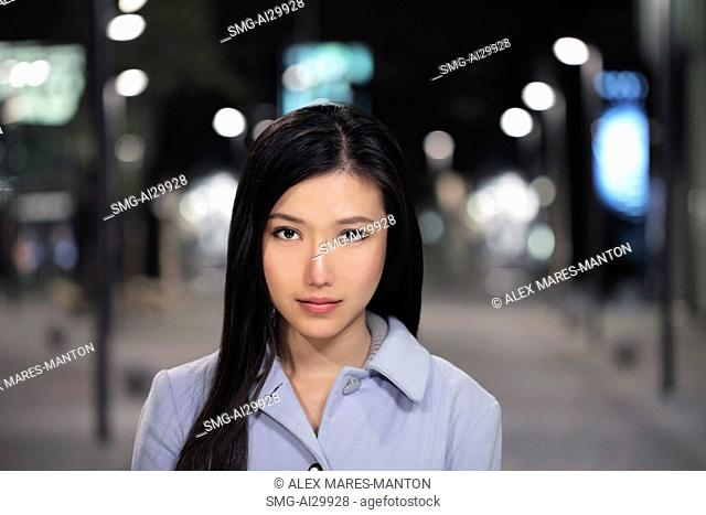Head shot of young woman on the street at night