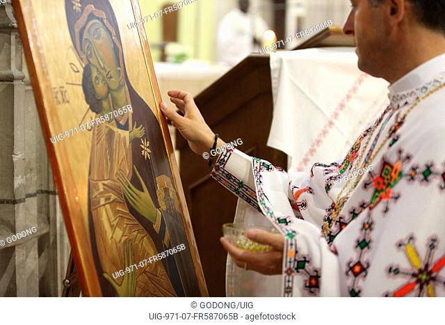 Melkite (Greek-catholic) priest blessing icons in Sainte Foy church
