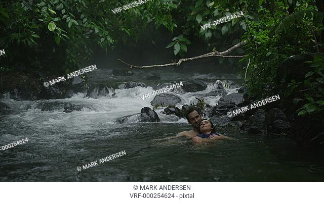 Wide shot of couple relaxing in flowing river / Arenal, La Fortuna, Costa Rica