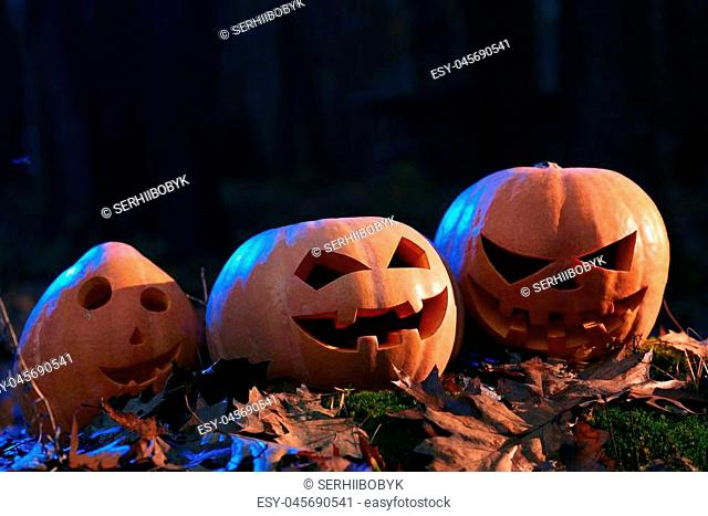 Close up of hand made three different orange pumpkins, fun, surprised and angry, with big eyes and funny smile. Prepare for Halloween party
