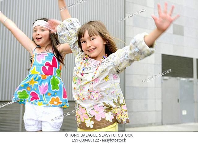 Two little girls dancing in the city with gray building in background