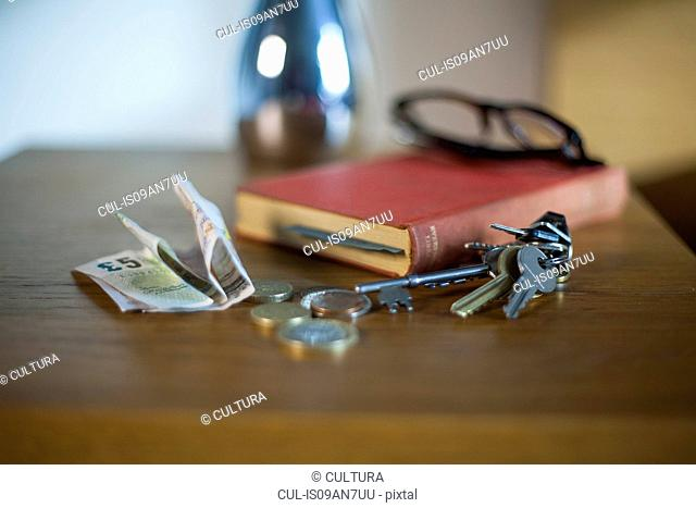 Bank notes, coins, book, keys and reading glasses