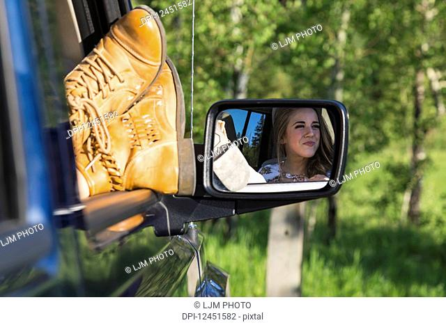 A female passenger with her feet out the window of the vehicle during a rest stop on a road trip; Edmonton, Alberta, Canada