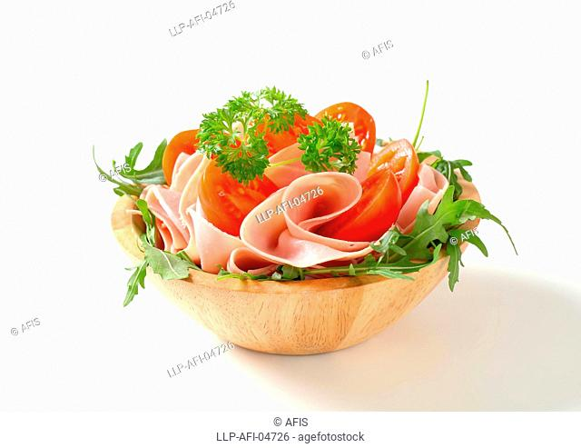 Sliced ham with arugula and tomatoes