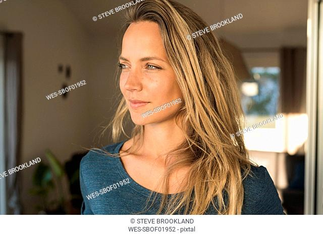 Portrait of blond woman at home looking sideways