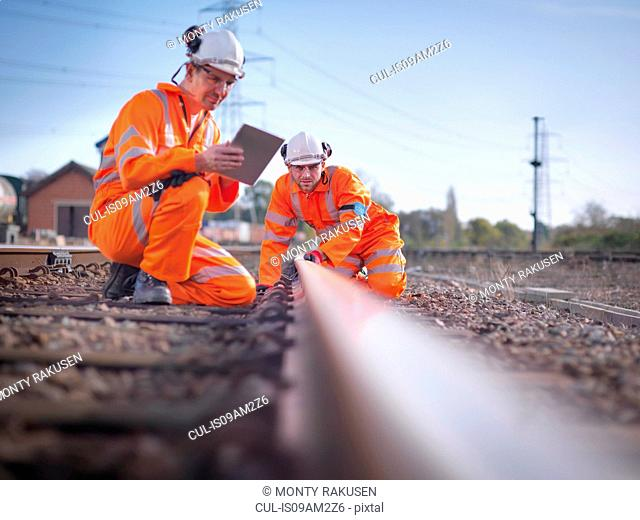 Railway maintenance workers using digital tablet to inspect track