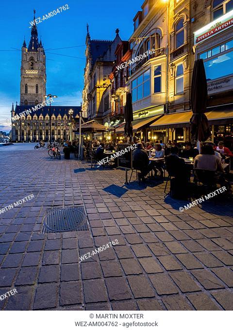 Belgium, Ghent, Sint-Baafsplein with belfry, cloth hall, restaurants and theater at dusk