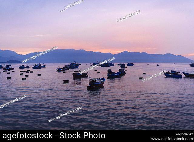 Large group of fisherman in traditional fishing boats on lake at sunrise, mountains in the distance