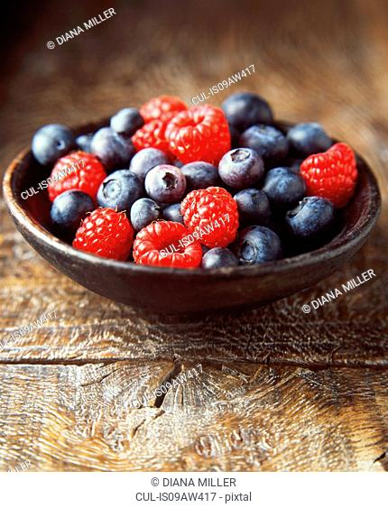 Fresh raspberries and blueberries in a wooden bowl, close-up