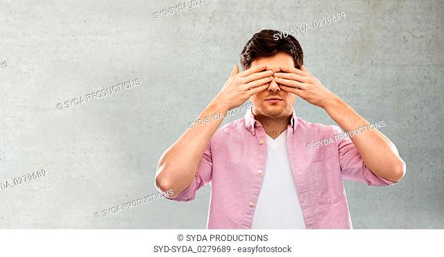 man closing his eyes by hands over concrete wall