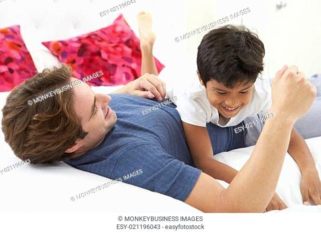 Father And Son Playing In Bed Together