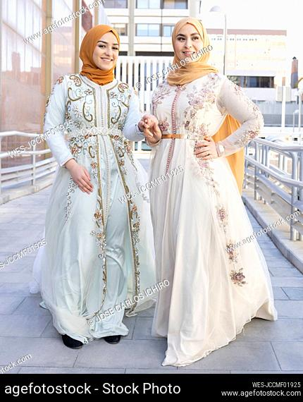Friends in fashionable dress holding hands while standing on bridge