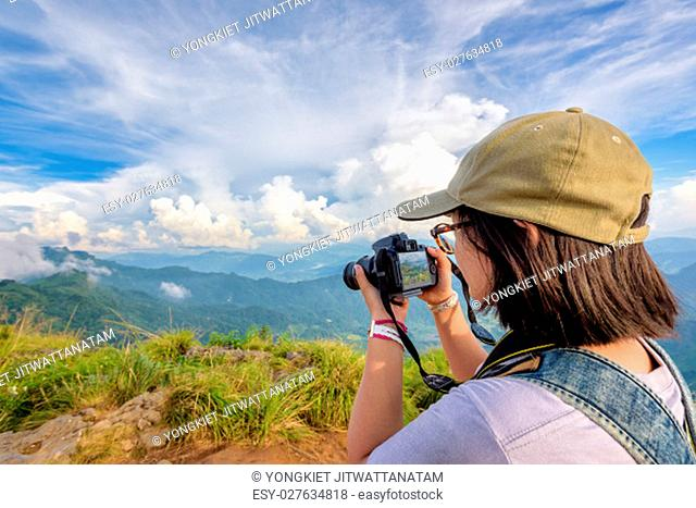 Hiker asian teens girl with backpack looking photo on digital camera is beautiful landscape natural of sierra and sky during sunset on mountain at Phu Chi Fa...