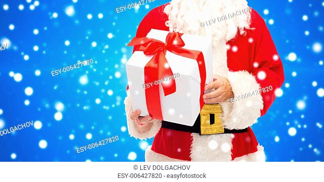 christmas, holidays and people concept - close up of santa claus with gift box over blue snowy background