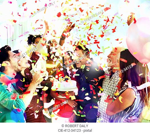 Family throwing confetti celebrating birthday party with cake