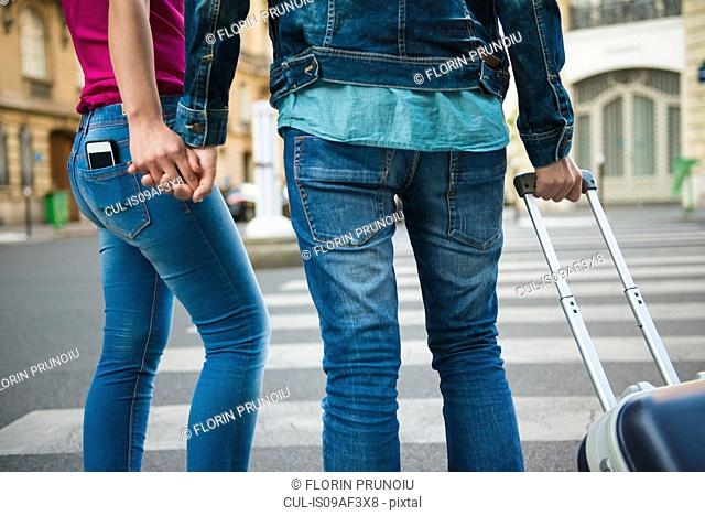 Young couple at crossing with wheeled suitcase, Paris, France