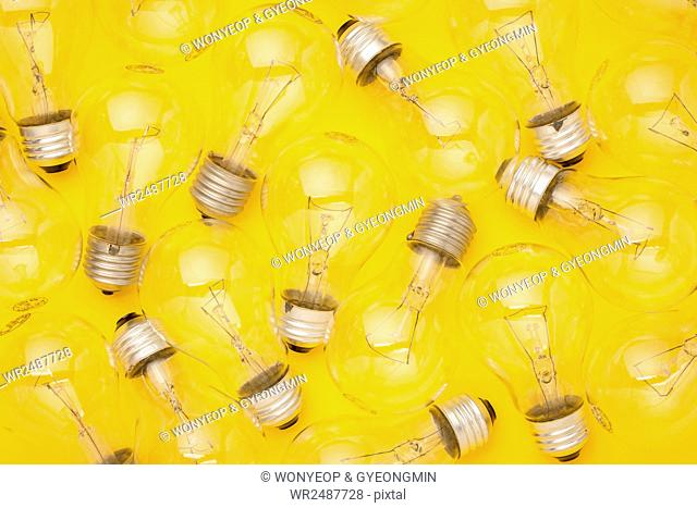 Lots of transparent lightbulbs against yellow