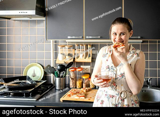 Portrait of happy woman eating homemade pizza in the kitchen