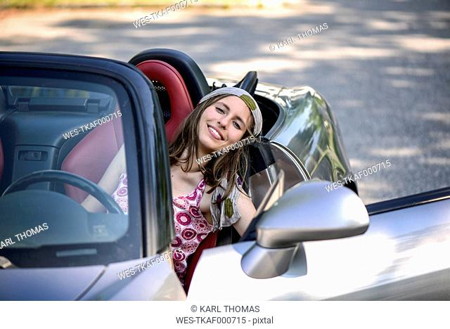 Portrait of smiling young woman in a convertible