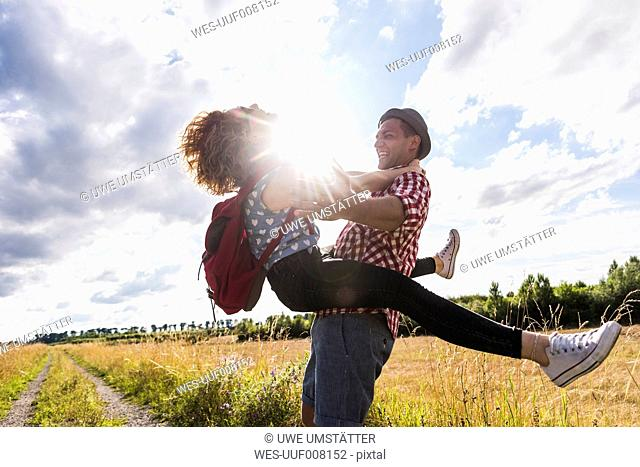 Enthusiastic young couple on field path