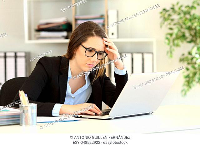 Worried office worker reading bad online news in a laptop