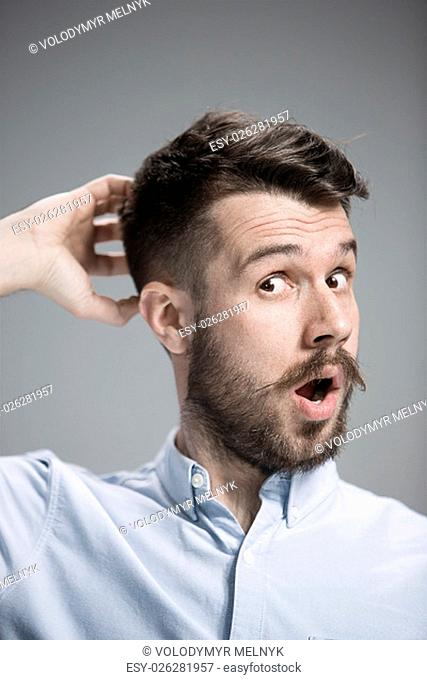 Portrait of young man with shocked facial expression over gray background