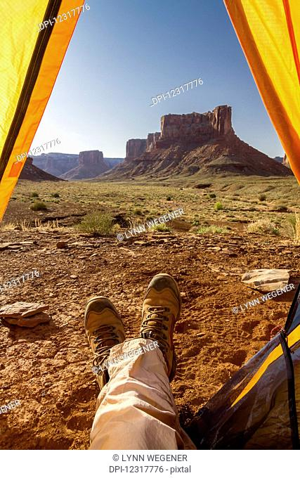 View of a camper's feet out of a tent viewing rock cliffs, Canyonlands National Park; Utah, United States of America