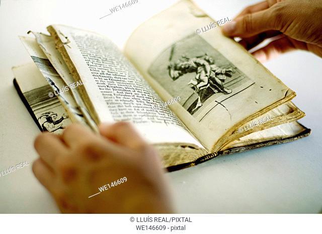 woman hands flipping through an old book