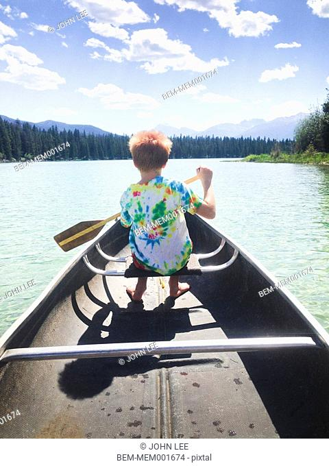 Caucasian boy rowing canoe on still lake