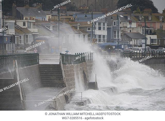 PENZANCE, CORNWALL, UK - 14 April, 2019 - A small group of pensioners get caught out by a large wave crashes against the harbour wall and over the lighthouse at...